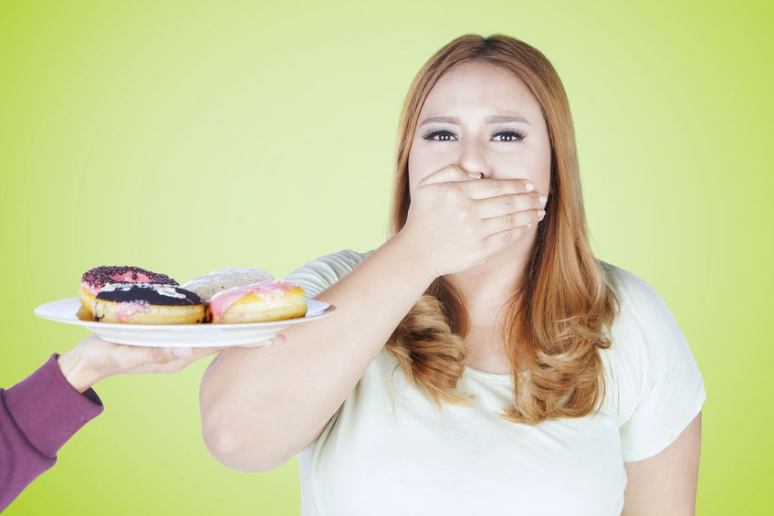 67348799 - portrait of young woman closed her mouth while refuses a plate of donuts